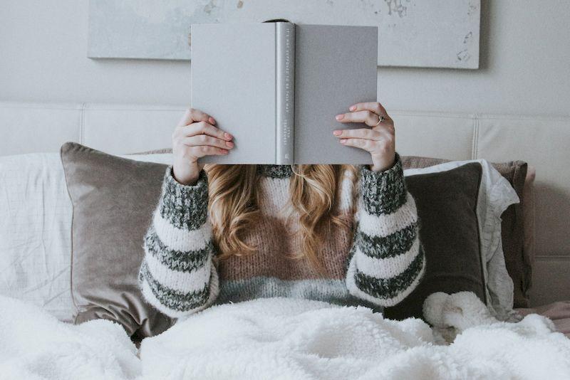 девушка читает книгу в постели